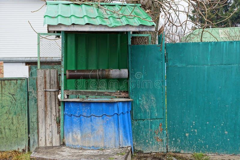 Gammalt järn väl av grön färg på gatan nära staketet arkivbild