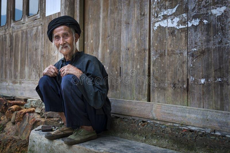 Gammalt kinesiskt mansammanträde på dörren av en gammal byggnad i byn av Dazhai i Kina royaltyfria foton