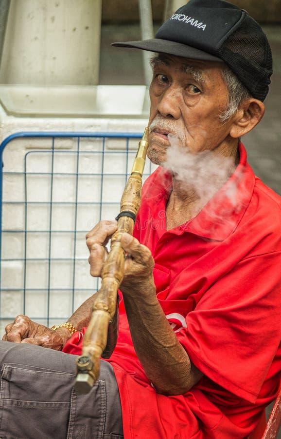 Gammalt kinesiskt röka för man arkivbild