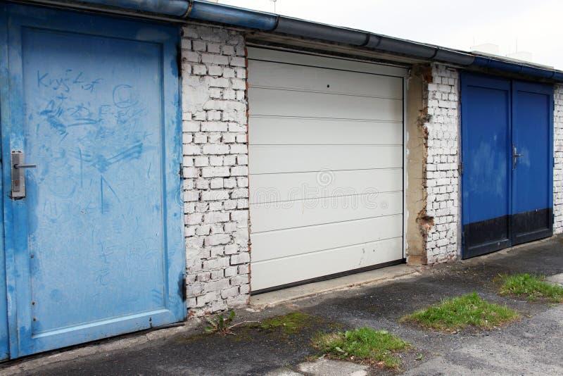 Gammalt kontra nytt, område av garagedörrar arkivbilder