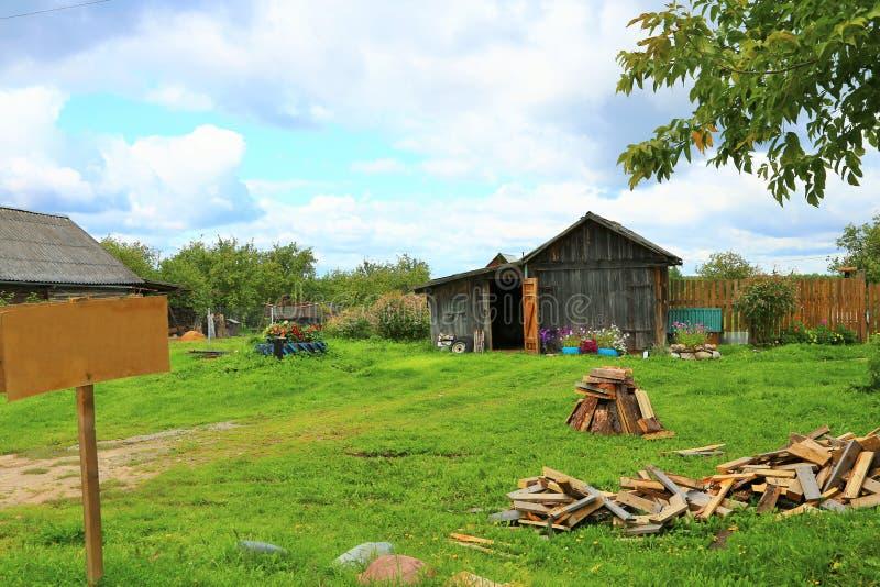 Gammalt lantligt trähus i ryssby i solig dag för sommar med ett tecken royaltyfri fotografi