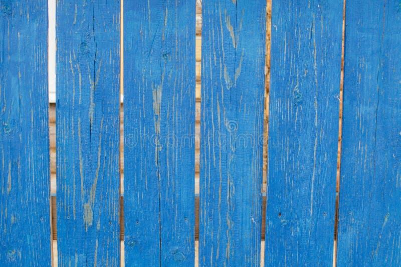 Gammalt lantligt trästaket med sjaskig blå målarfärg arkivfoton