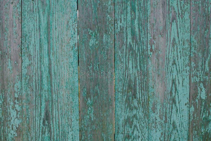 Gammalt lantligt trästaket med sjaskig och skalande turkosmålarfärg arkivfoton