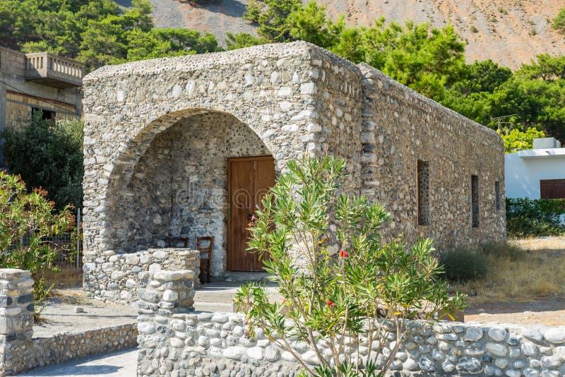 Gammalt litet hus för tegelstenkubform med trädörren Huset i den Grekland bygden arkivbilder