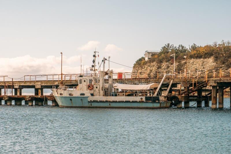 Gammalt litet skepp eller fartyg på den konkreta pir för havsport arkivbilder