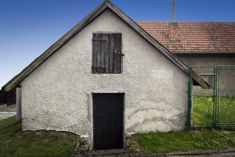 Gammalt litet vitt hus med ett träfönster och en dörr och en trädgård arkivbilder