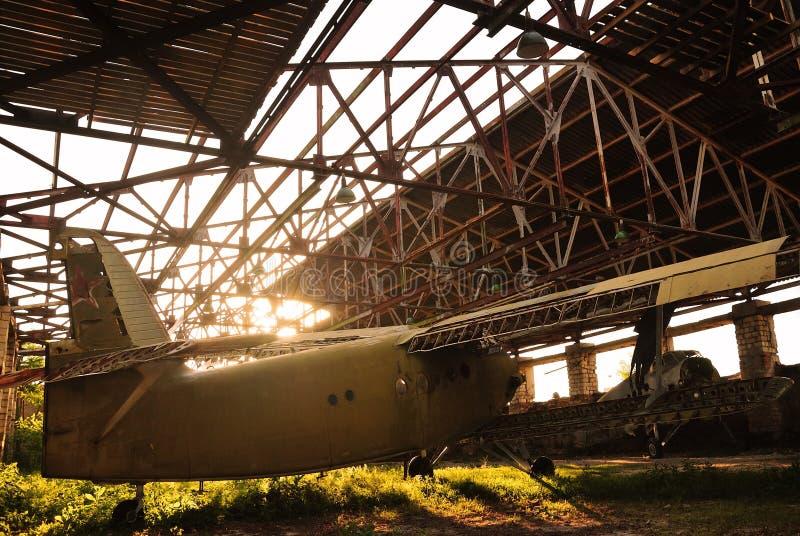 Gammalt ljust flygplan i en övergiven hangar royaltyfria bilder