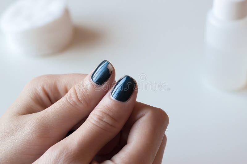 Gammalt mörker - blå manikyr Sjaskigt spika polermedel Kvinnahänder på den vita tabellen arkivbilder
