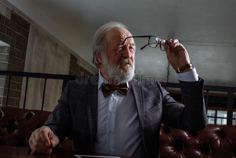 Gammalt manligt försöka att se ho de durty exponeringsglasen pensionären torkar upp exponeringsglas arkivbild