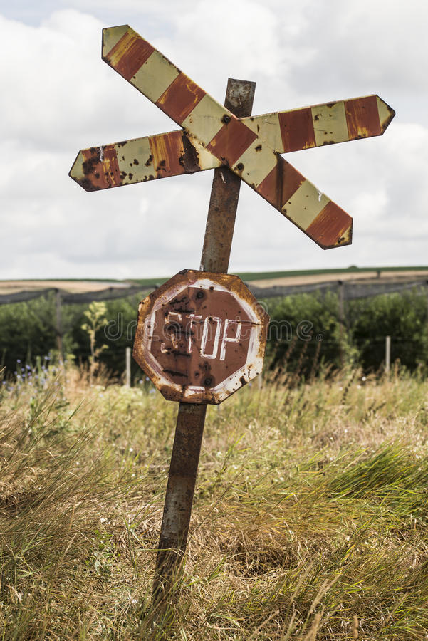 Gammalt och rostigt järnvägtecken med stoppbokstäver arkivfoto