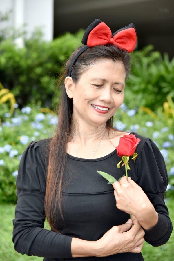 Gammalt olikt kvinnligt högt le med en ros royaltyfria bilder