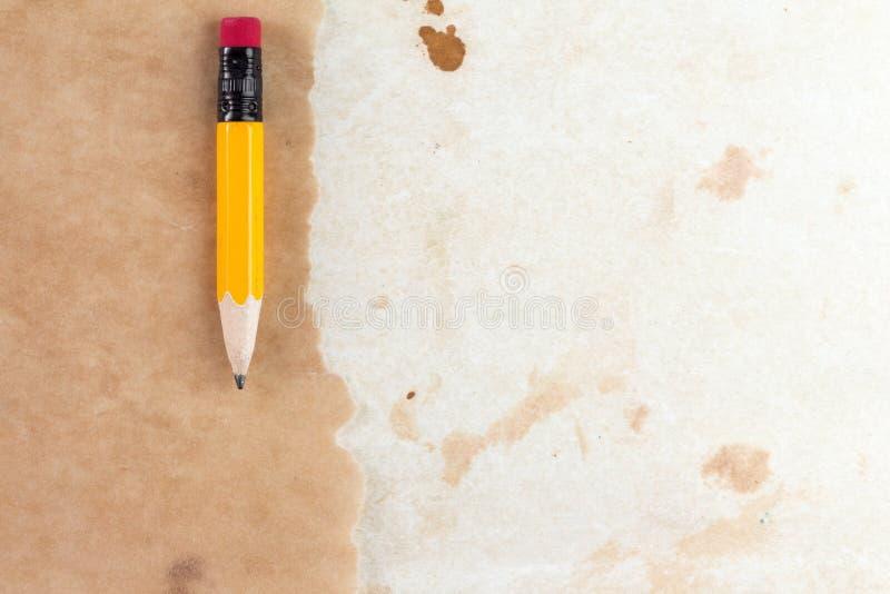 Gammalt papper med en kort blyertspenna royaltyfri foto