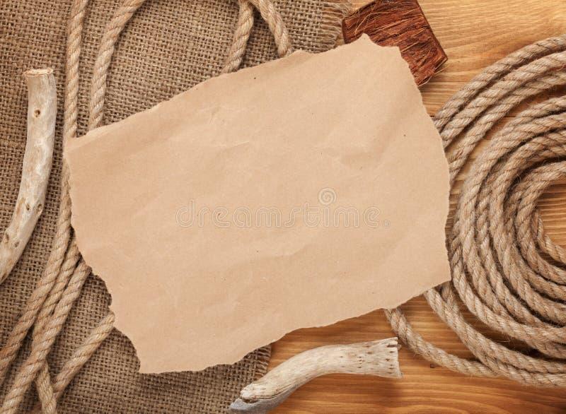 Gammalt papper och rep på trätexturerad bakgrund arkivbilder