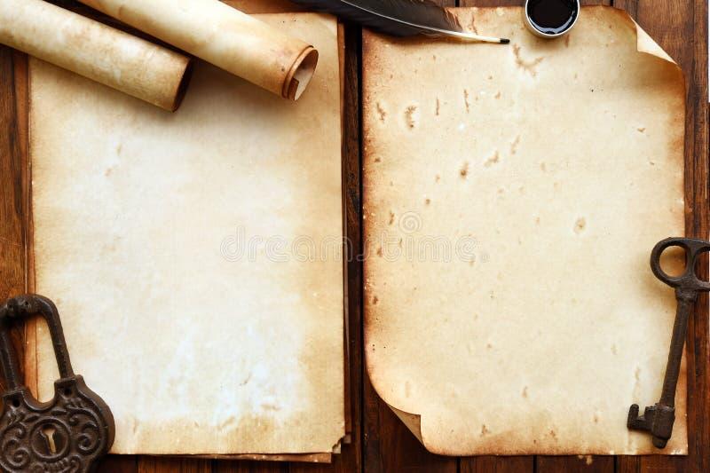 Gammalt papper på brun wood textur med fjädern och färgpulver arkivfoton