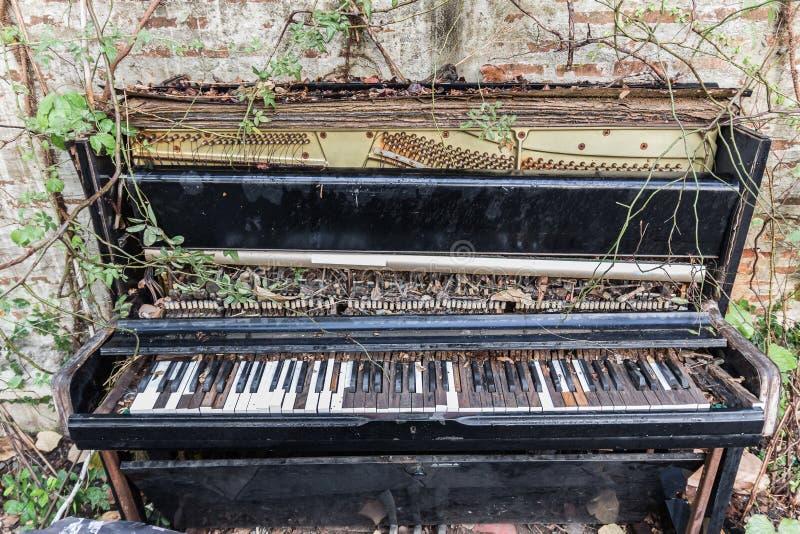 Gammalt piano med betongväggen och bladet arkivfoton