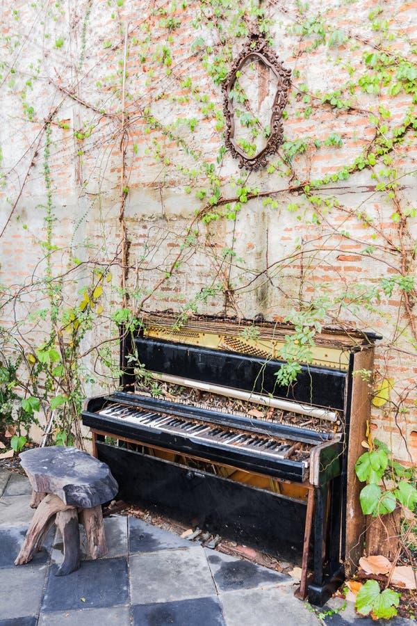 Gammalt piano med betongväggen och bladet royaltyfri foto