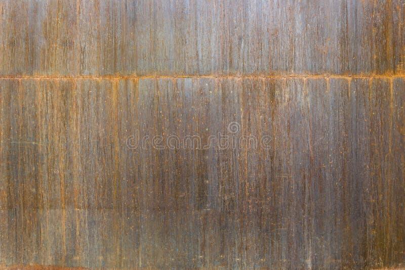 Gammalt rostat metallark Rostig yttersida som orsakas av oxideringjärn med apelsinen, och knäckt brunt färgar För designarbetstex royaltyfri bild