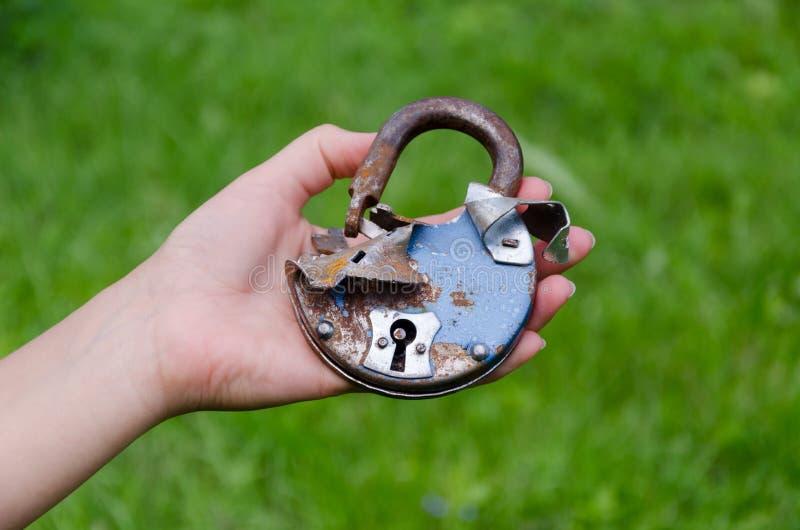 Gammalt rostigt brutet dörrlås på den utomhus- manhanden arkivfoton