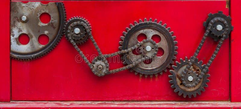 Gammalt rostigt kedjekugghjul på en röd backgro arkivfoton