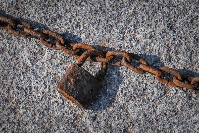 Gammalt rostigt lås som hänger på en kedja på grå asfaltbakgrund royaltyfria bilder