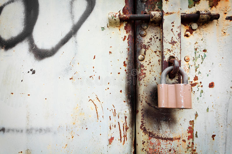 Gammalt rostigt låser på grunge belägger med metall dörren royaltyfri bild