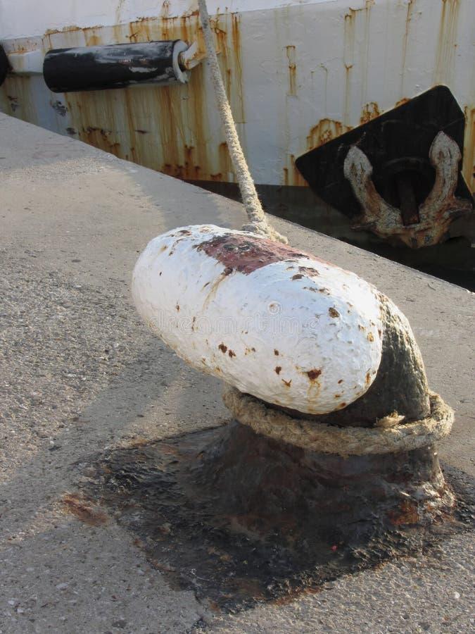 Gammalt rostigt pollare och rep på en traditionell hamnpir med den red ut fiskebåten i bakgrunden fotografering för bildbyråer