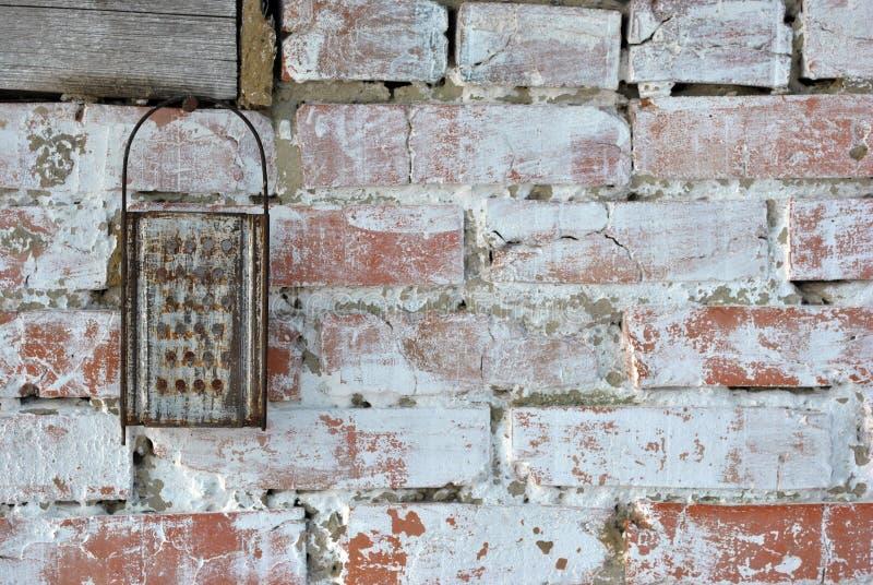 Gammalt rostigt rivjärn som hänger på en tegelstenvägg som kalkas lantlig ladugård royaltyfri fotografi