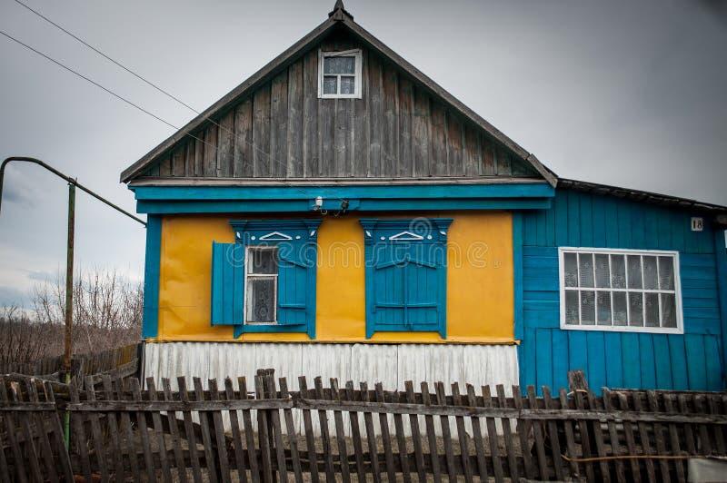 Gammalt ryssbyhus med blåa träslutare arkivfoton