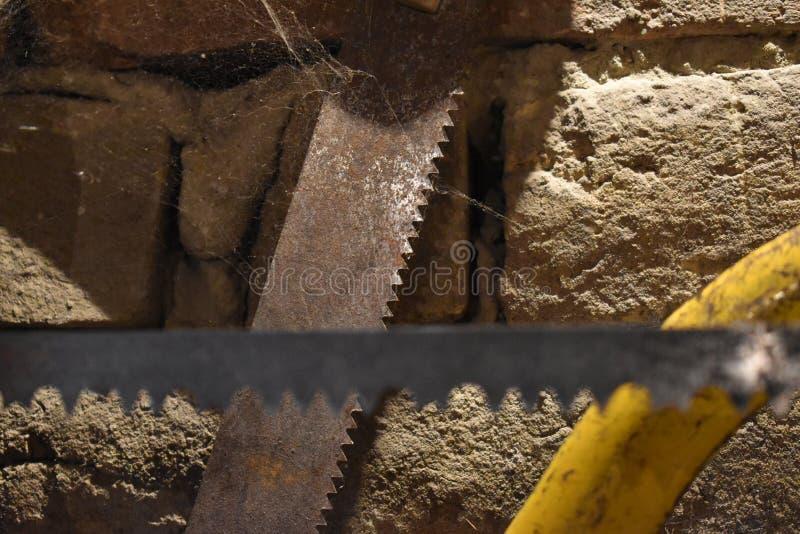 Gammalt sågverk, två såg blad framme av den dammiga tegelstenväggen arkivbilder