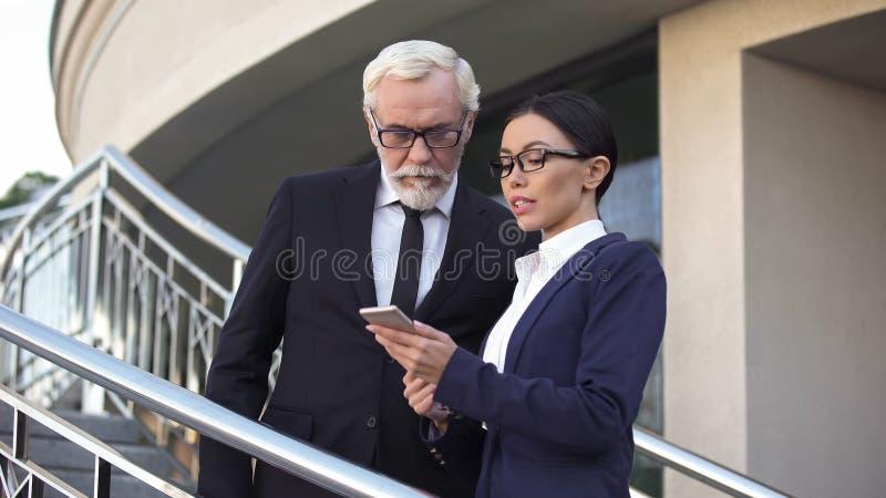 Gammalt schema för hållande ögonen på möte för affärsman i smartphone med den unga sekreteraren royaltyfria bilder