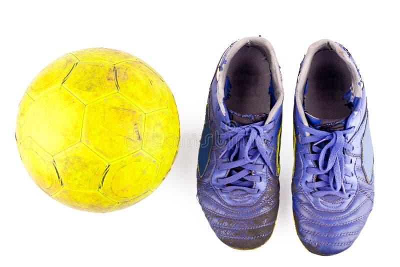 Gammalt skadat syntetiskt futsal och skor och gammal gul futsal boll på isolerat vitt objekt för inomhus fotboll för bakgrund arkivbilder