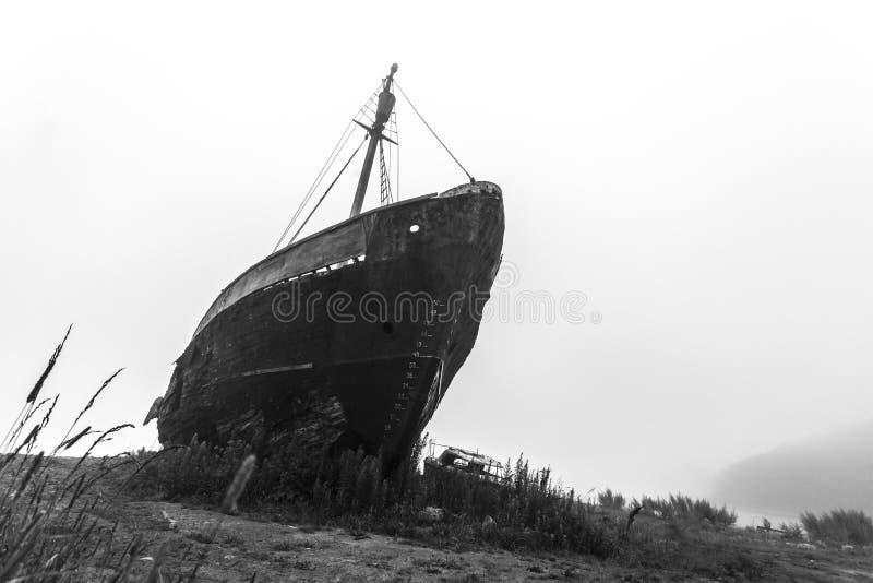 Gammalt skeppsbrutet skepp i den svartvita bilden f?r morgonmist royaltyfri foto