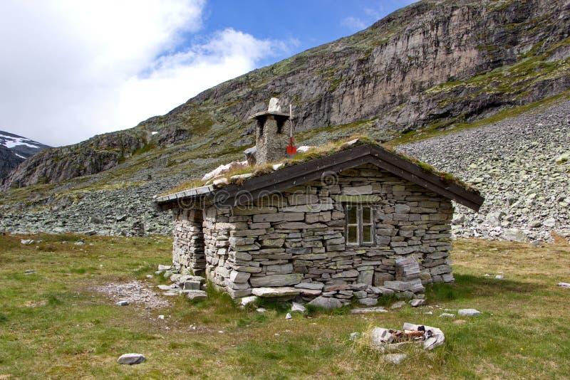 Gammalt skydd som göras av stenar och trä i norsk vildmark arkivfoton