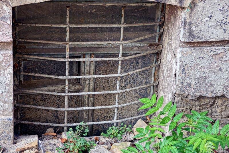 Gammalt smutsigt fönster i källaren i gräset arkivbilder