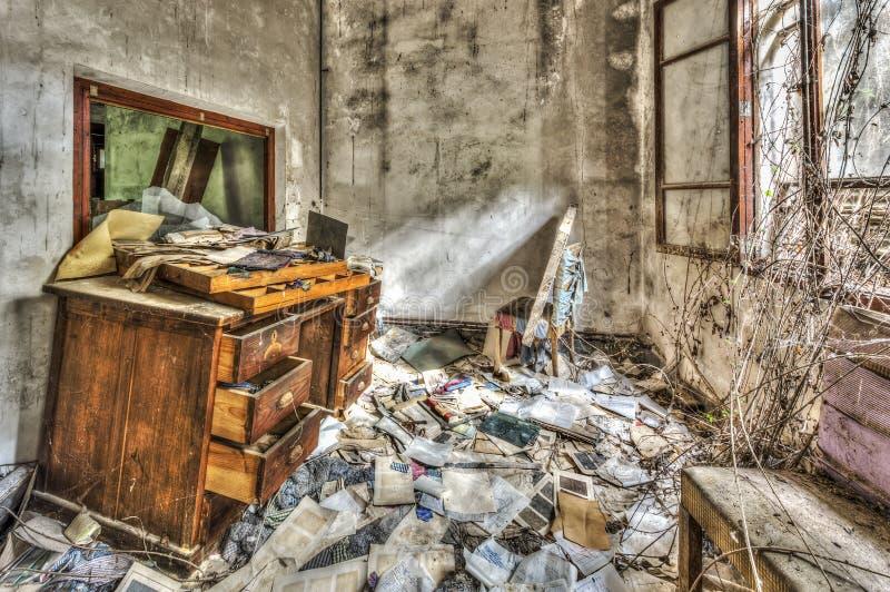 Gammalt smutsigt kontorsmöblemang i en övergiven fabrik fotografering för bildbyråer
