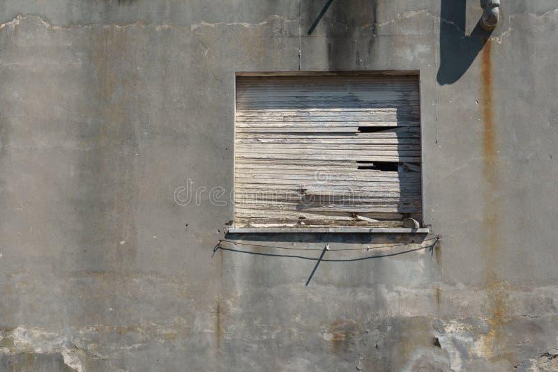 Gammalt som stigas ombord upp fönster i en betongvägg arkivfoto