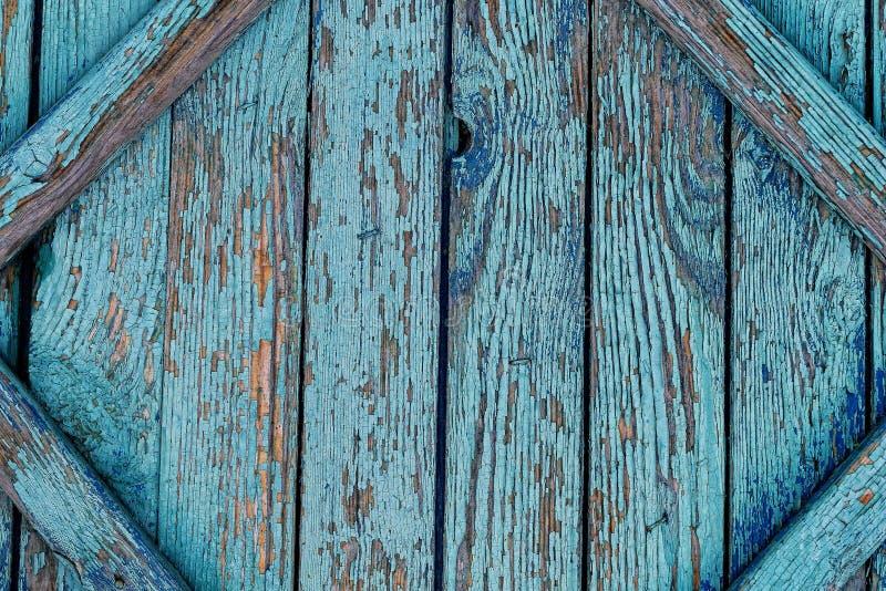 Gammalt sprucket staket med blå sjaskig målarfärg royaltyfria foton