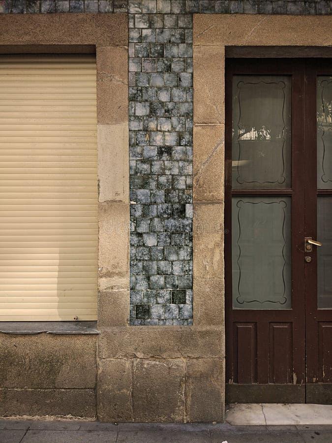 Gammalt stängt fönster med träslutaren och en dörr med genomskinligt exponeringsglas i en granitstenvägg och blåtttegelplattor royaltyfri fotografi