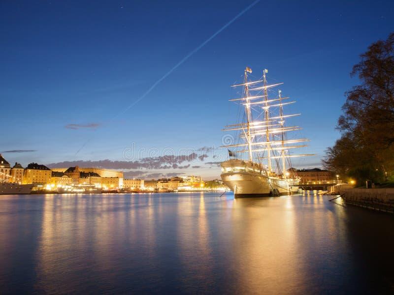 Gammalt stad och skepp i Stockholm på natten arkivbilder