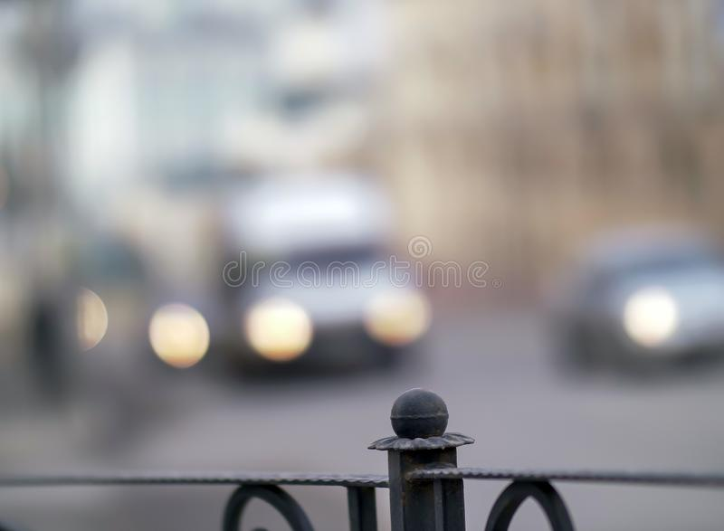 Gammalt staket för metall på en suddig bakgrund av bilbillyktor royaltyfria foton