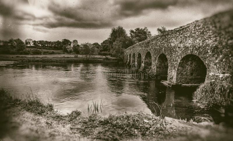 Gammalt stena bron med bågar, lynnig himmel, landskap i sepia arkivfoton