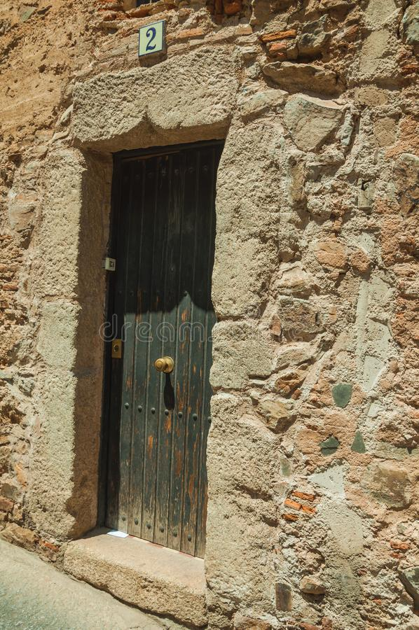 Gammalt stena byggnadsfasaden med den stängda trädörren på Caceres royaltyfri foto