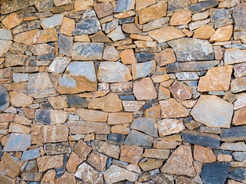 Gammalt stena väggen av stora stenar F?r kvarteryttersida f?r tappning grov bakgrund royaltyfri foto