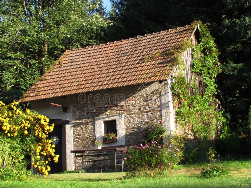 Gammalt stenbylantbrukarhem i en blommande trädgård arkivfoto