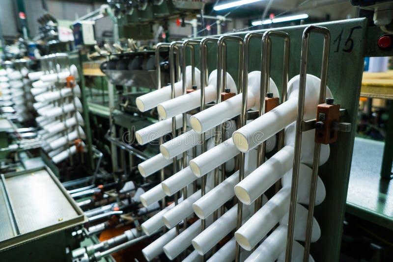 Gammalt stuckit tyg Textilfabrik i roterande produktionslinje och roterande en maskineri- och utrustningproduktion arkivbild