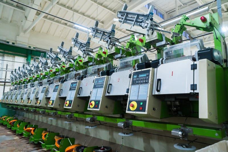 Gammalt stuckit tyg Textilfabrik i roterande produktionslinje och roterande en maskineri- och utrustningproduktion royaltyfria bilder