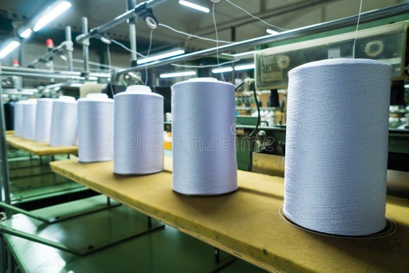 Gammalt stuckit tyg Textilfabrik i roterande produktionslinje och roterande en maskineri- och utrustningproduktion arkivfoton