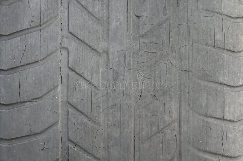 Gammalt svart gummihjul med sliten däckmönster och sprickor, sliten gammal däckmönster för bilgummihjul, gammal skadad sliten sva royaltyfria foton