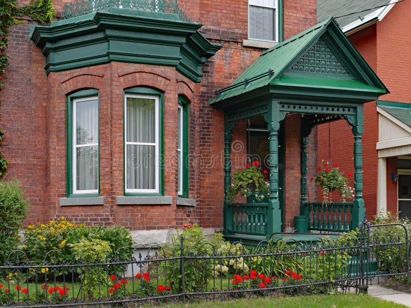 Gammalt tegelstenhus med fjärdfönstret royaltyfria foton
