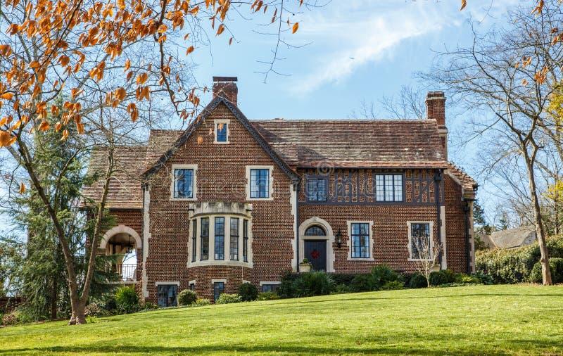 Gammalt tegelstenhus med klassiska Windows på grönt gräs arkivbilder